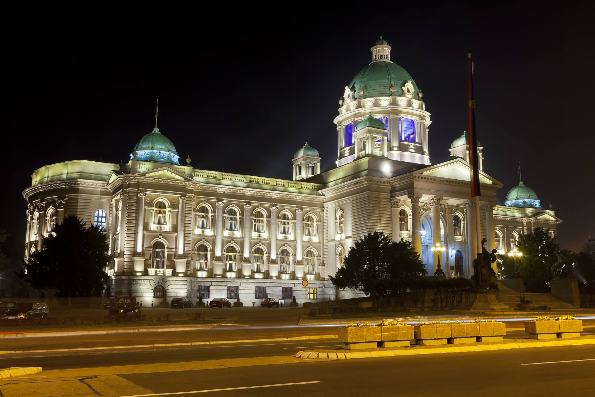 Serbian parliament photographed from the side at night.