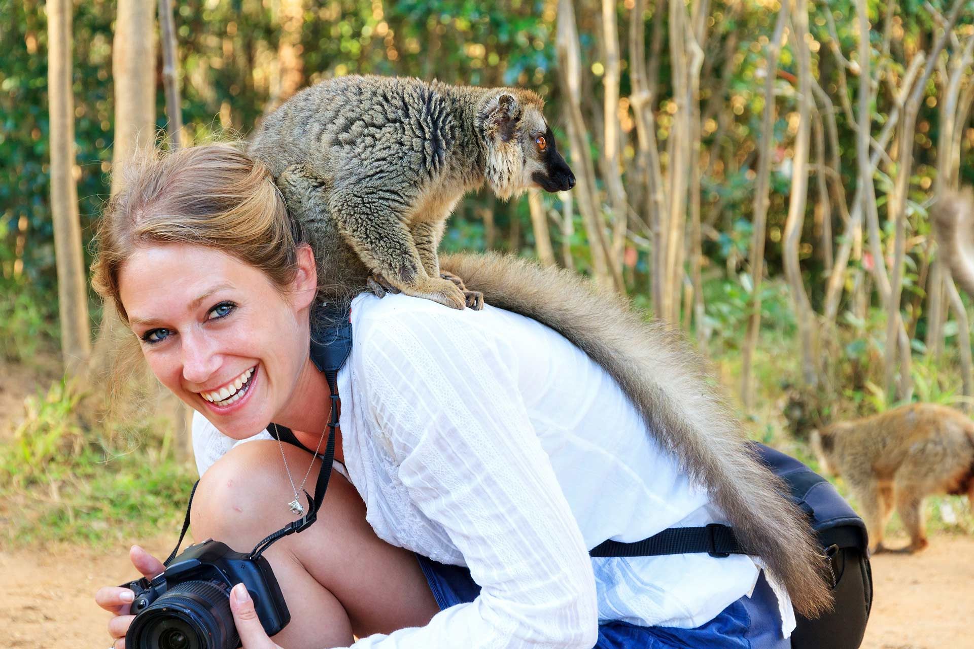 Lemur sits on the shoulder of a woman on the Nosy Be island