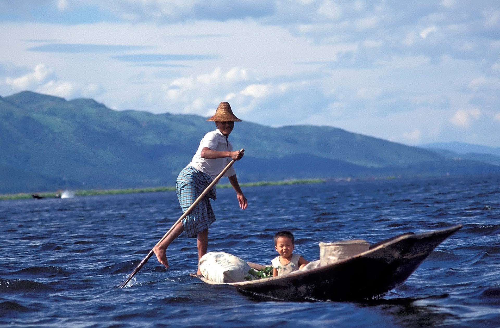 Child and fisherman rowing boat with one leg, Inle Lake, Myanmar