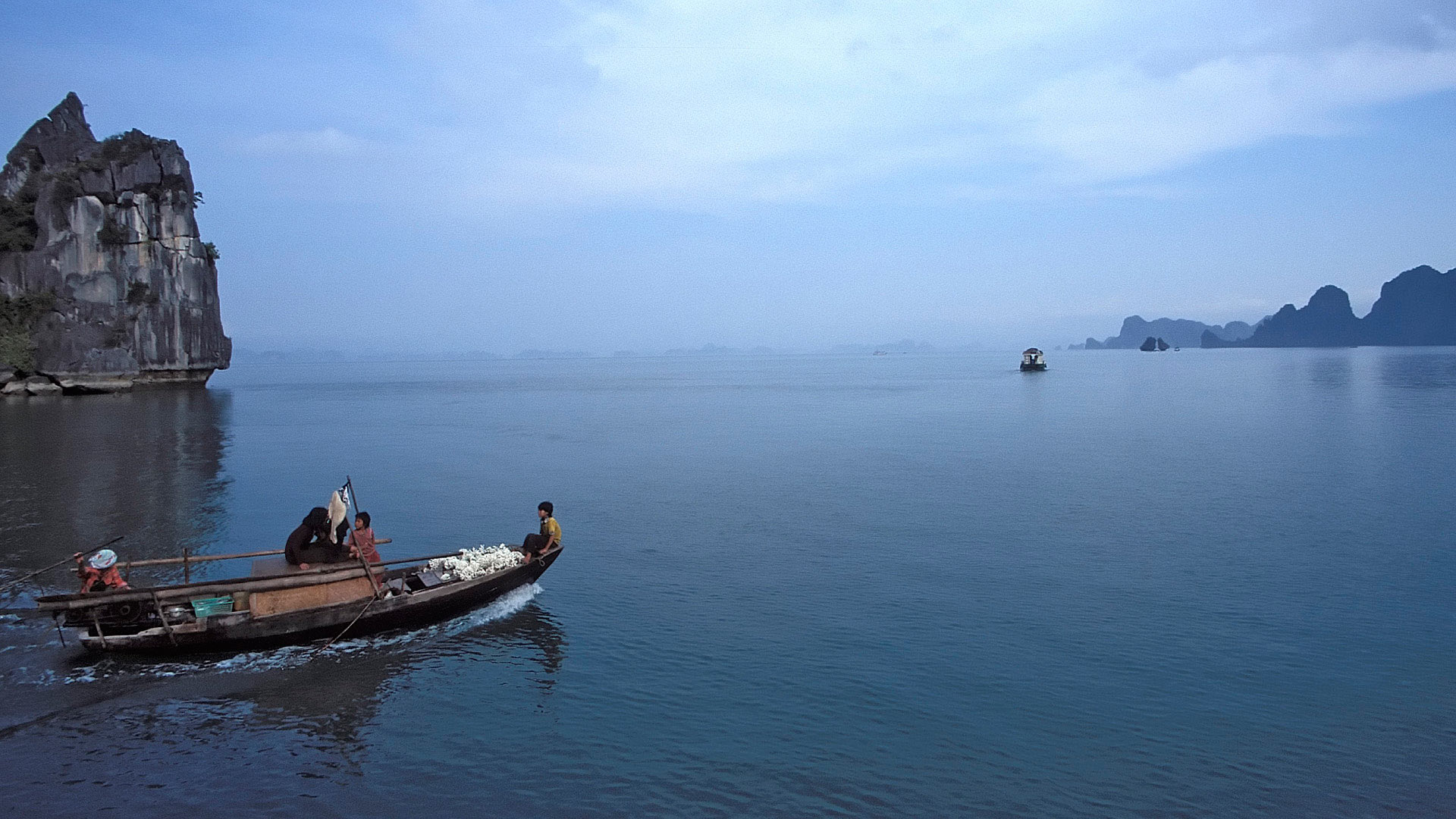 Boat travelling through the Limestone karsts and isles in various sizes and shapes in Ha Long Bay, Quang Ninh, Vietnam