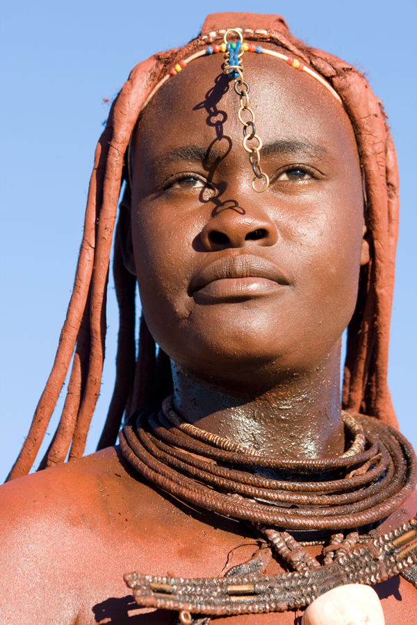 Himba woman portrait with traditional jewelry on blue sky background