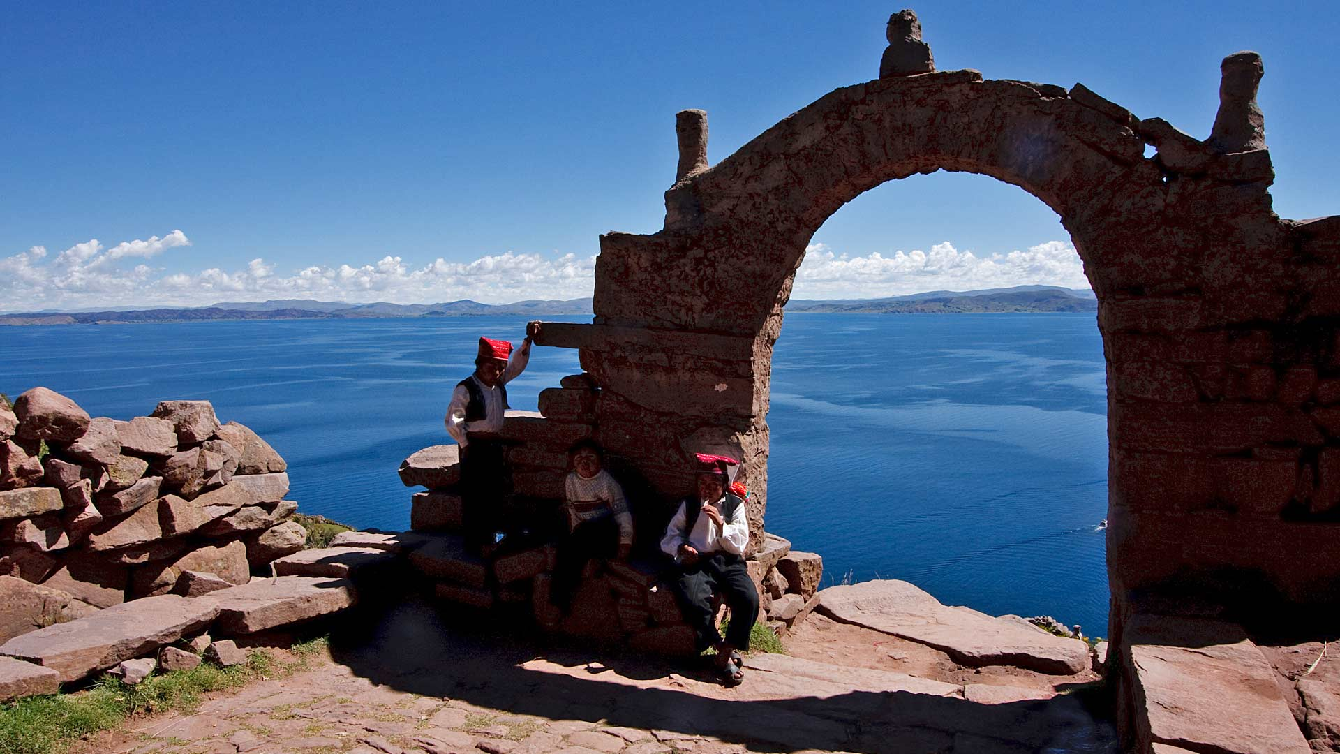 Taquile boys by an arch on Taquila Island overlooking Titicaca Lake