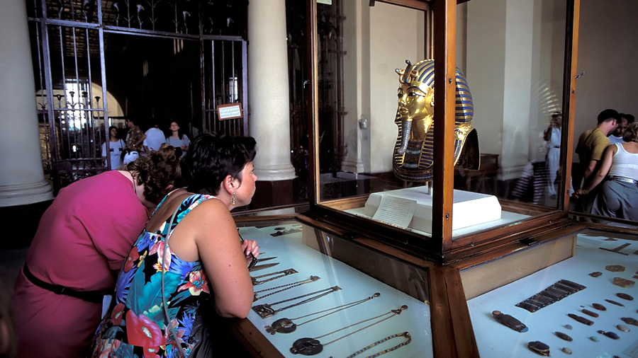 Woman looking in amazement at Tutankhamun's funerary mask on display at the Museum of Egyptian Antiquities