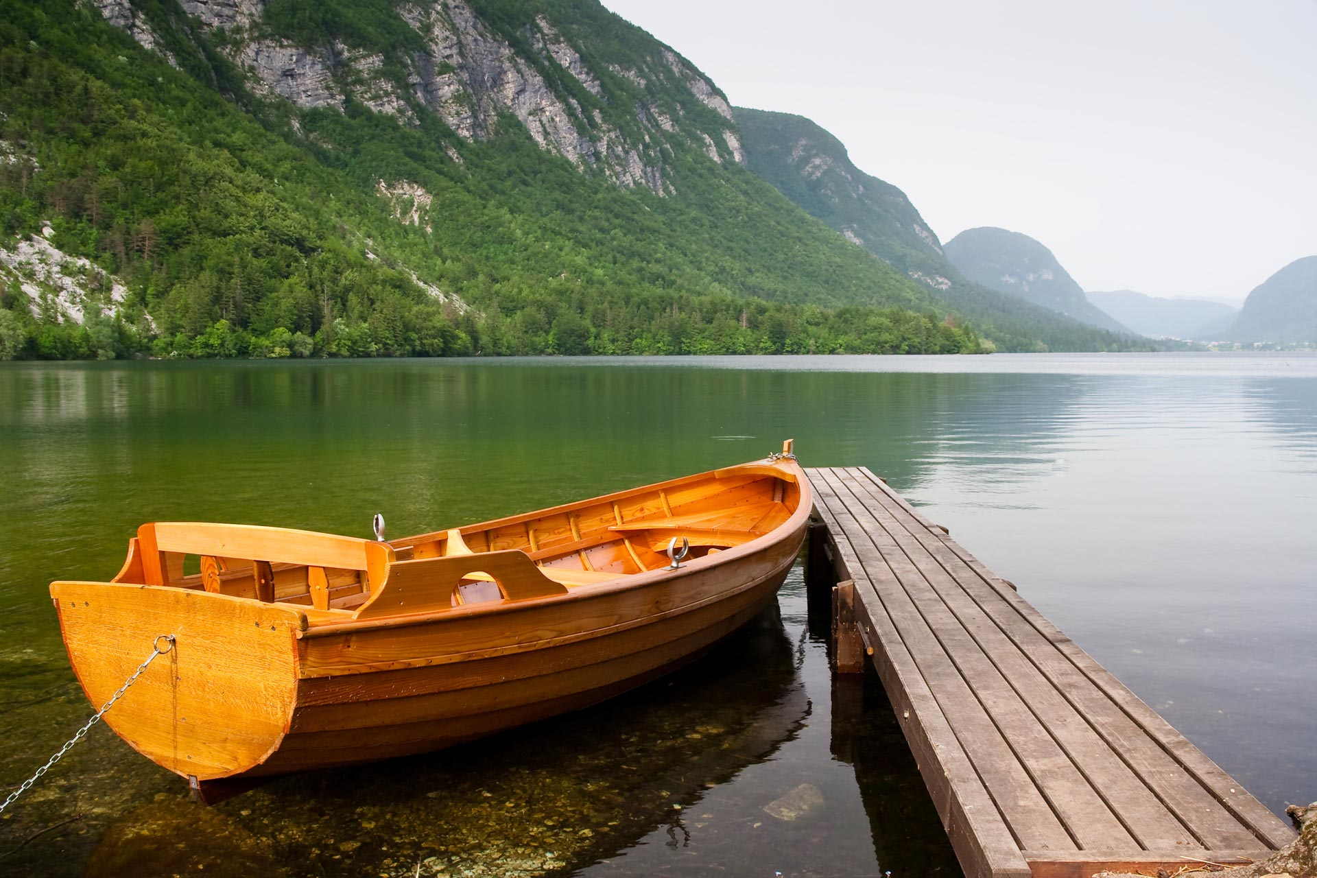 boat berth on the shore of bohinj lake in Slovenia with mountain as background. This photo truly expresses the tranquility and unsploit nature of the eastern europe country.