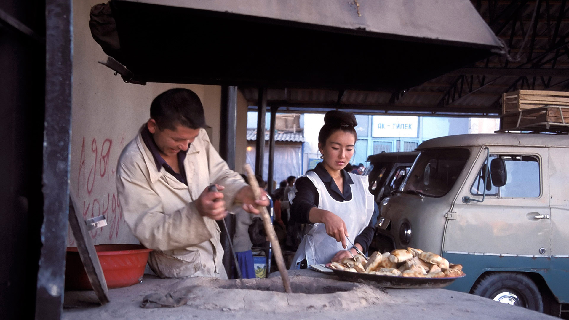 Man and woman making meat pies at a bazaar, Kyrgyzstan