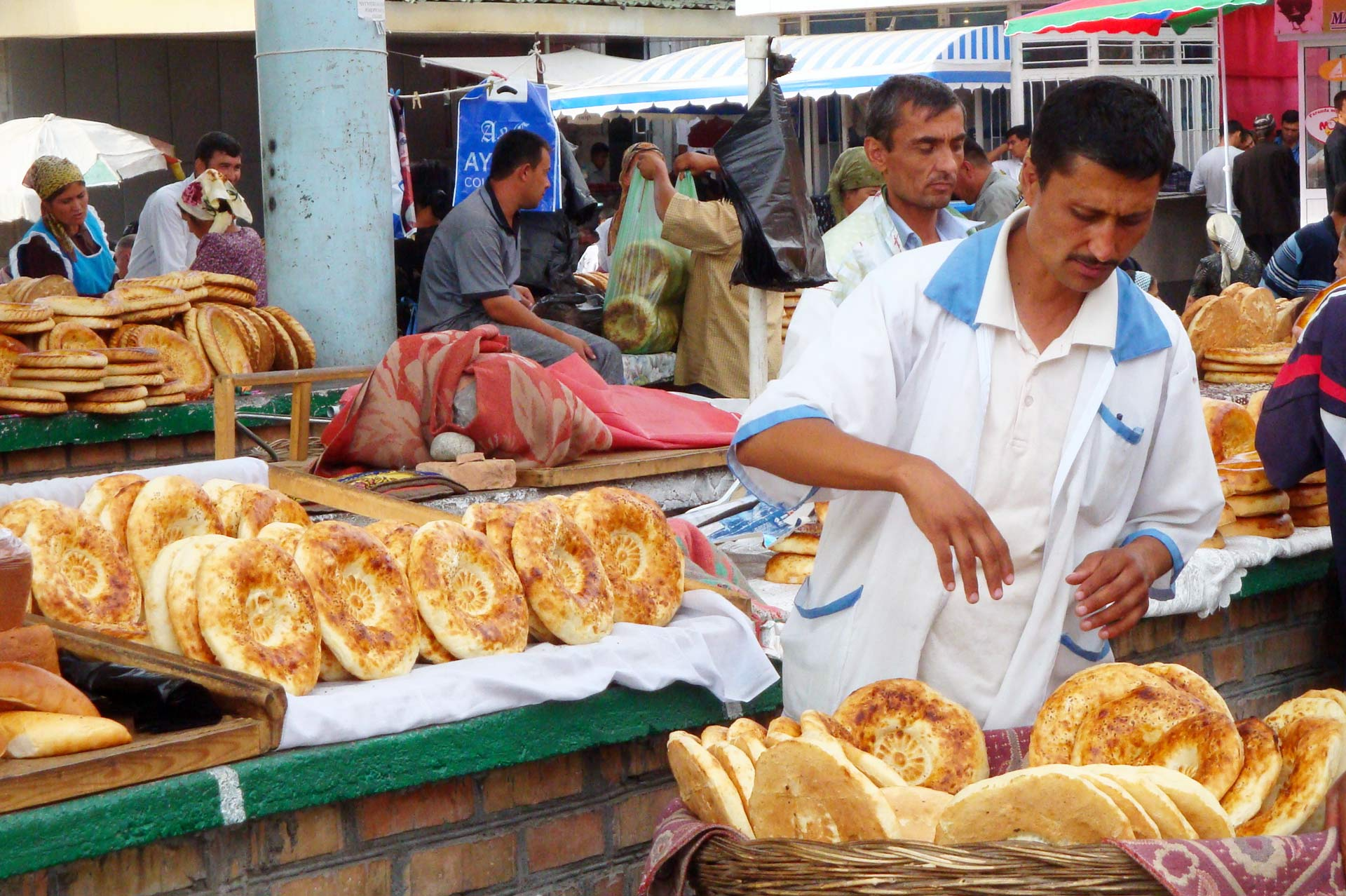 man selling traditional uzbek bread at main city market (bazaar)