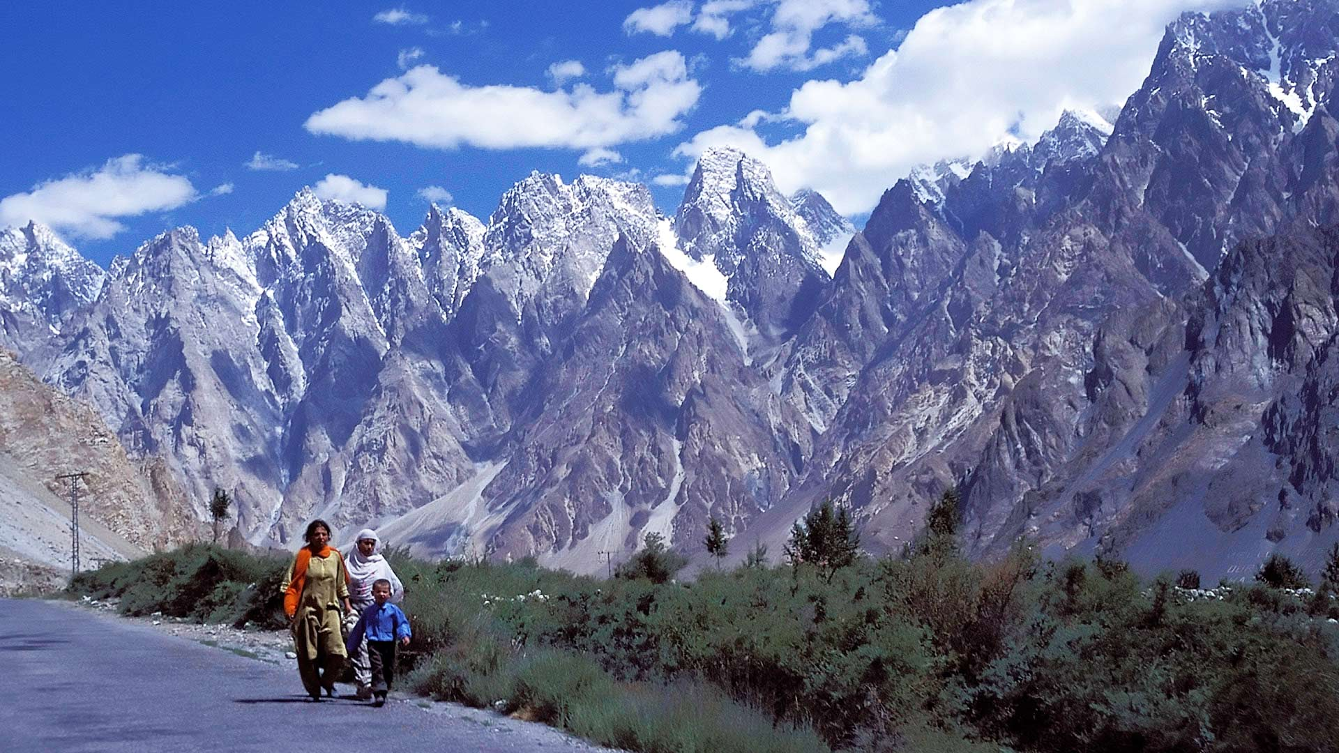 Women walking on the Karakoram Highway with the Little Karakoram Range in the background, Northern Areas, Pakistan