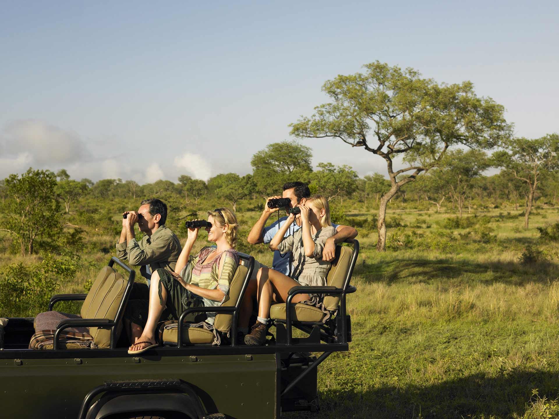 Tourists viewing game from an open safari vehicle