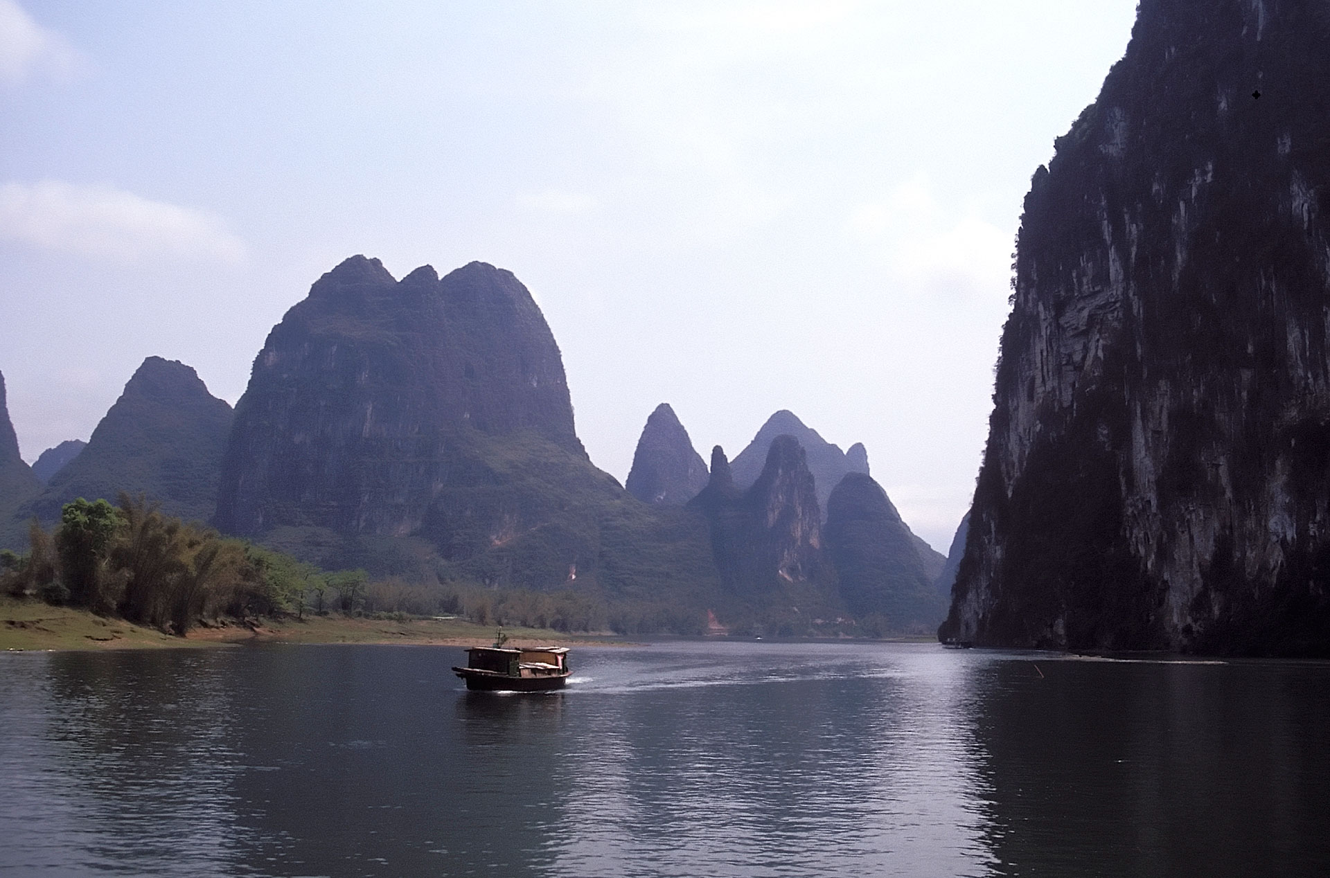 Boat on the Lijiang River surrounded by karst limestone formations, Guangxi, China