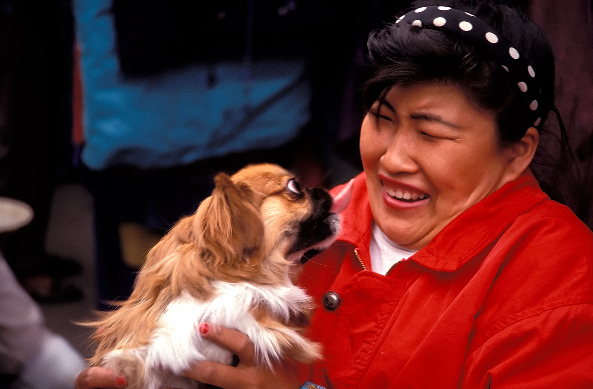 Woman holding a Pekinese dog, China