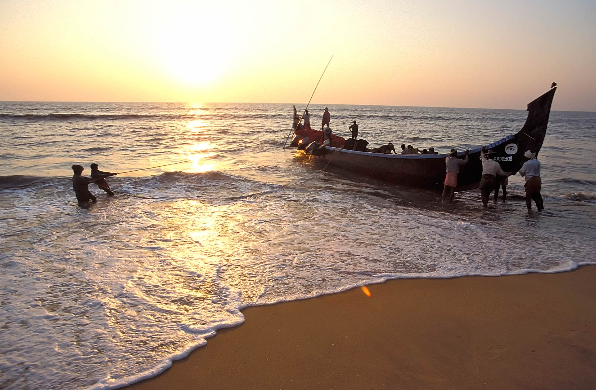 Fishermen bringing in the catch on Nattika Beach at sunset, Kerala, India