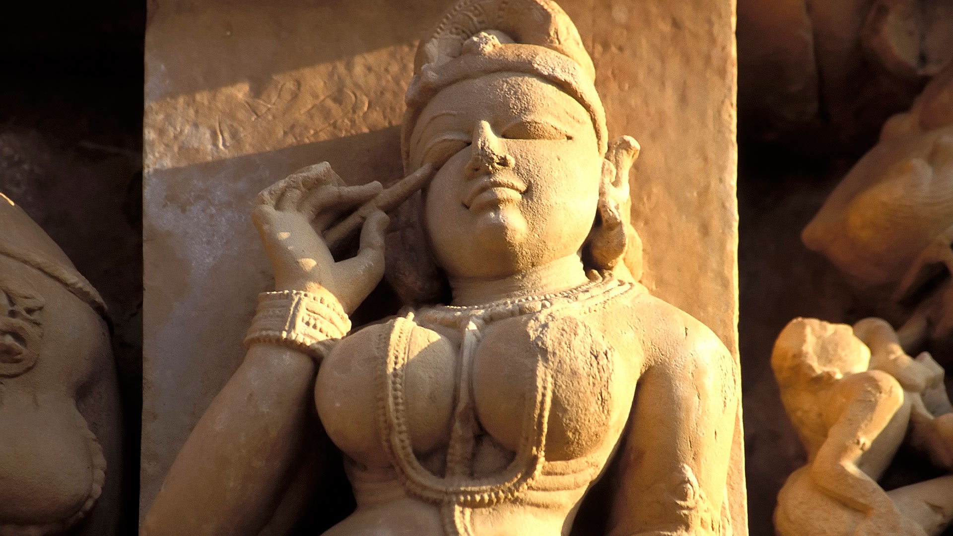 Apsara applying collyrium at the Parsvanath Temple located in the Eastern group of the Khajuraho Group of Monuments, Madhya Pradesh, India