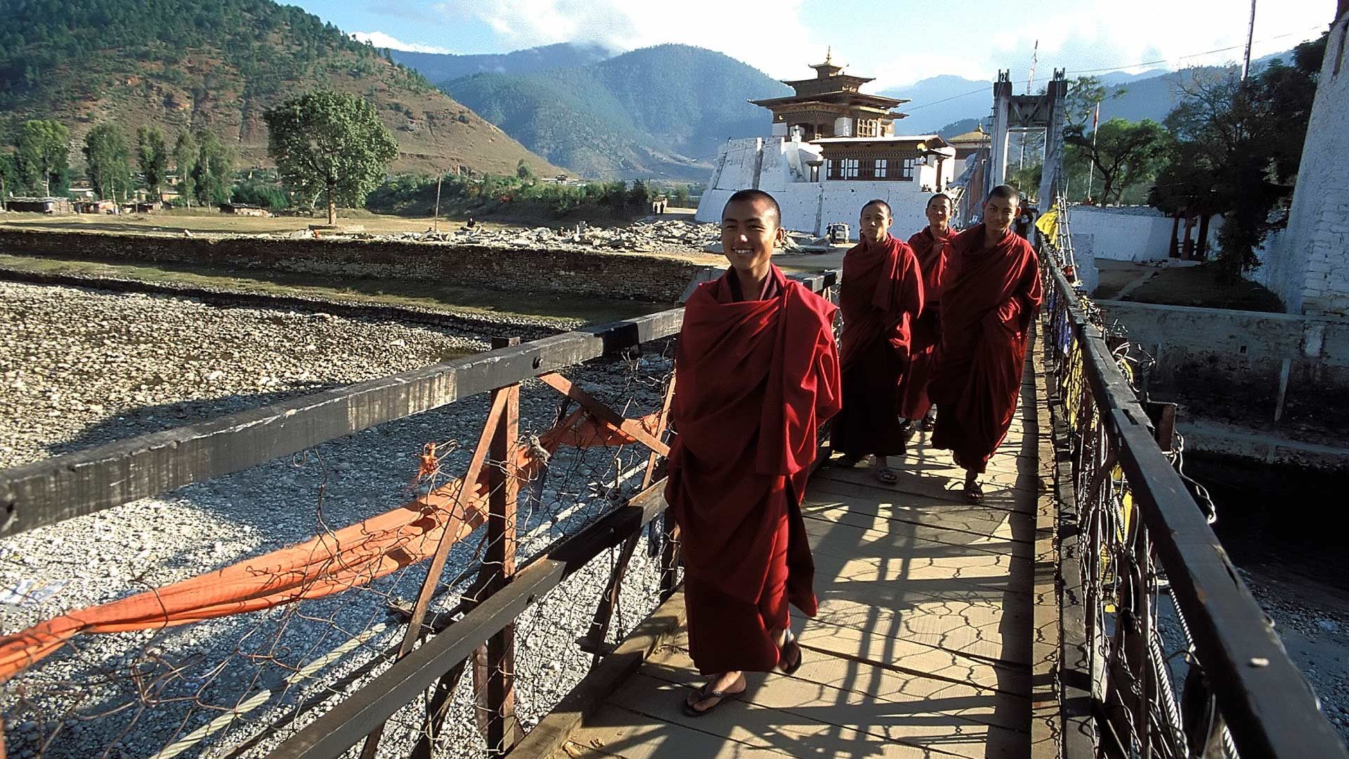 Buddhist monks on a suspension bridge over the Pho Chu River, Punakha Dzong, Phunaka District, Bhutan