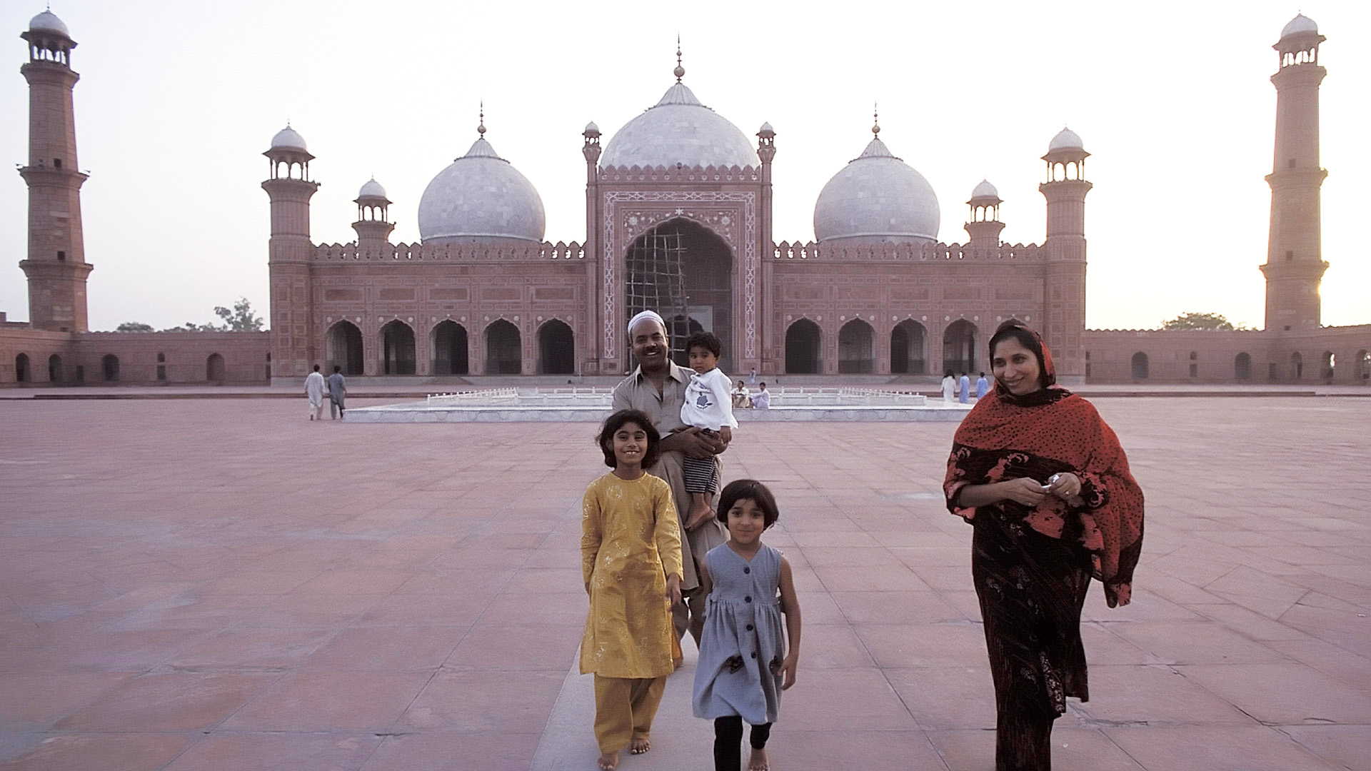 Family in the courtyard of the Badshahi Mosque at dusk, Lahore, Punjab, Pakistan