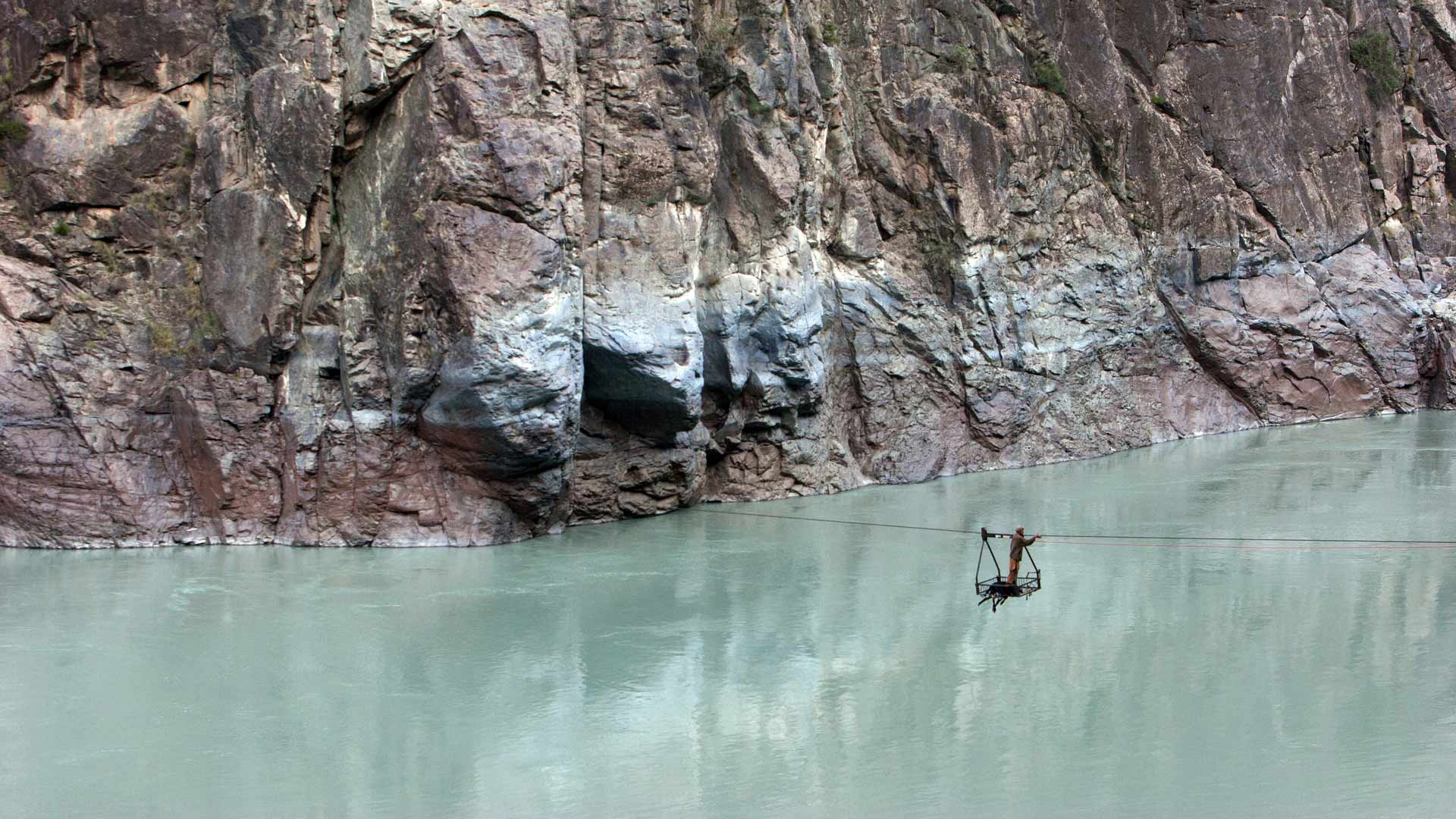 Man crossing the Indus River on a ropeway near Chilas, Northern Areas, Pakistan