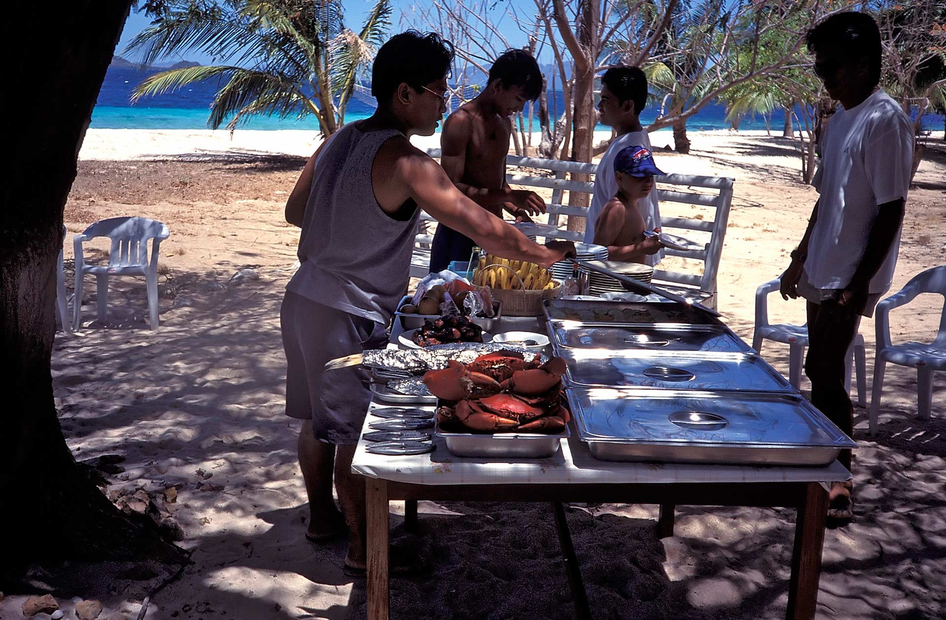 Men having a barbecue on the beach, Philippines