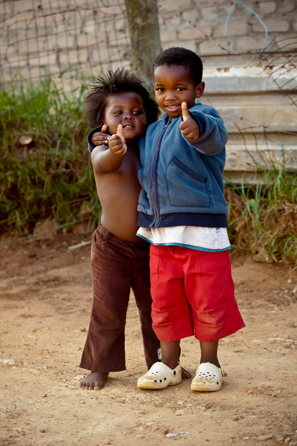 Two kids in the street showing a thumbs up to the photographer