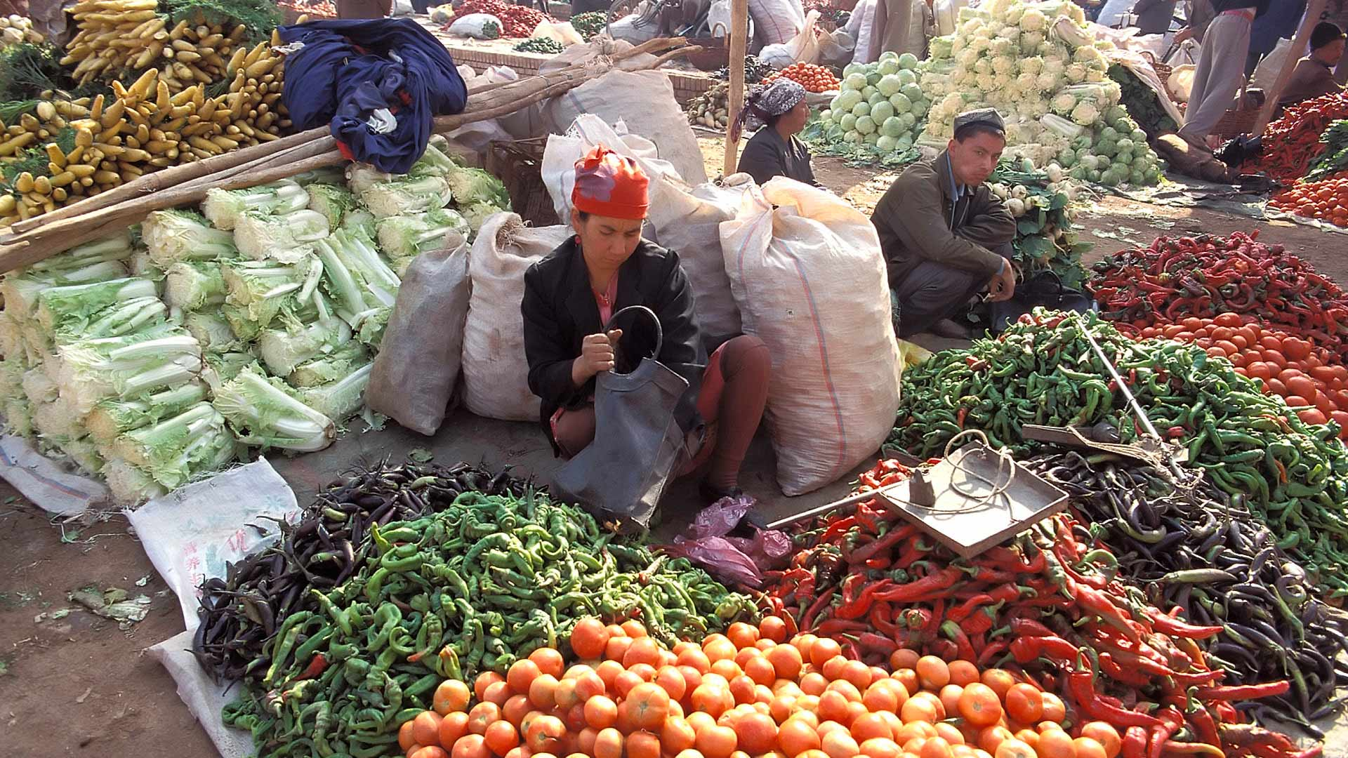 street vendors selling vegetables and herbs in the market