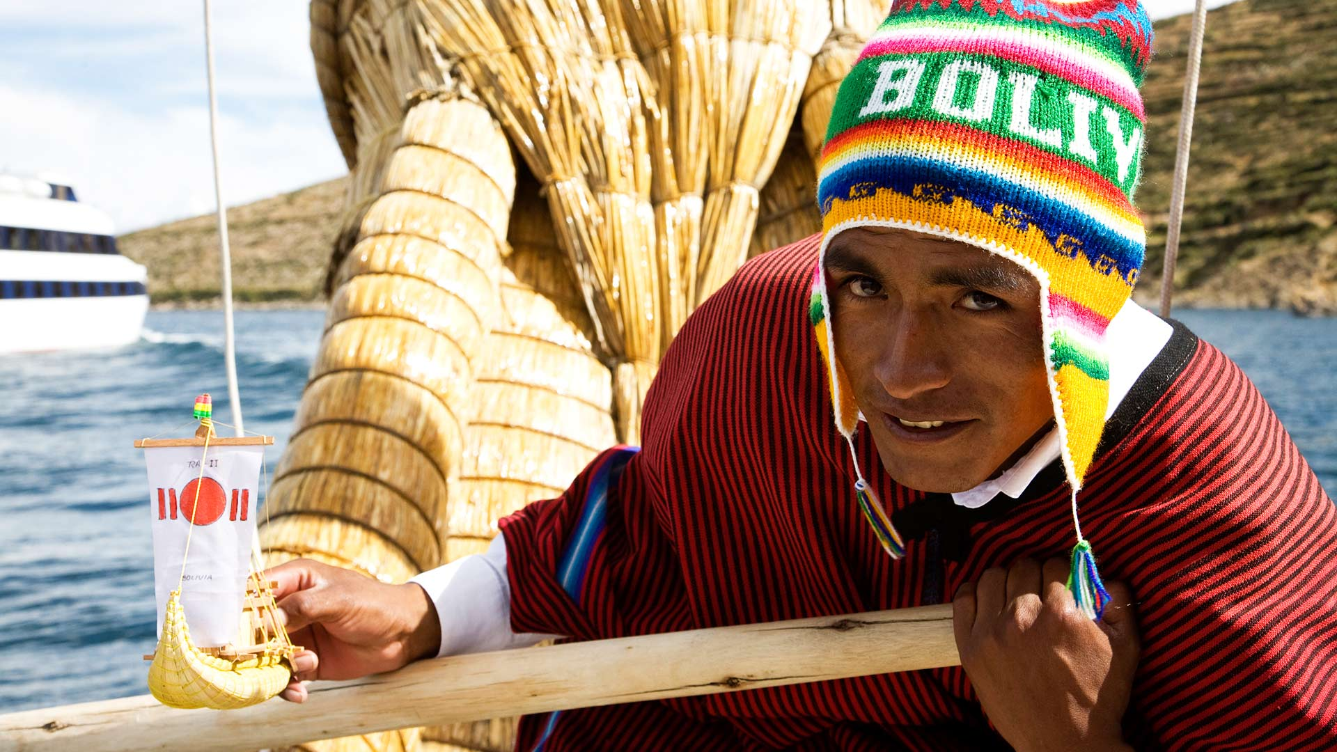 Aymara man dressed in traditional clothing rowing a tourist boat made of totora reeds around the Isla del Sol in Titicaca Lake